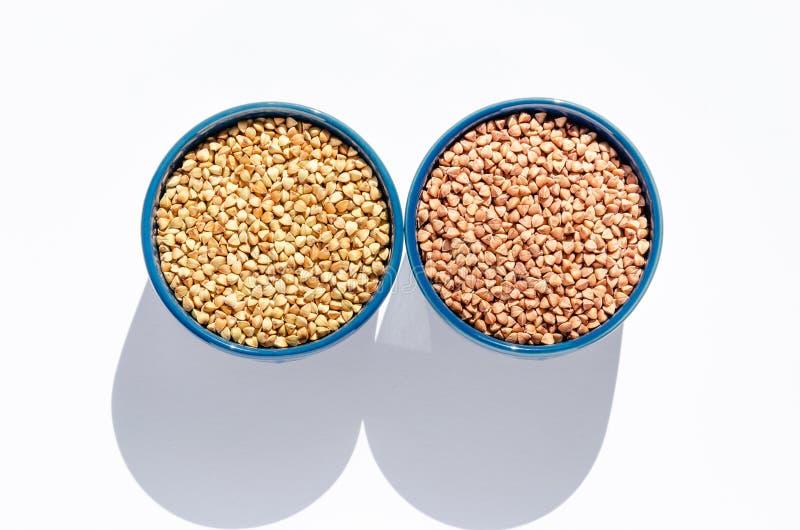 Twee blauwe ceramische kommen ruw groen en geroosterd boekweit op een witte achtergrond Gezond het Eten Concept Hoogste mening stock afbeeldingen