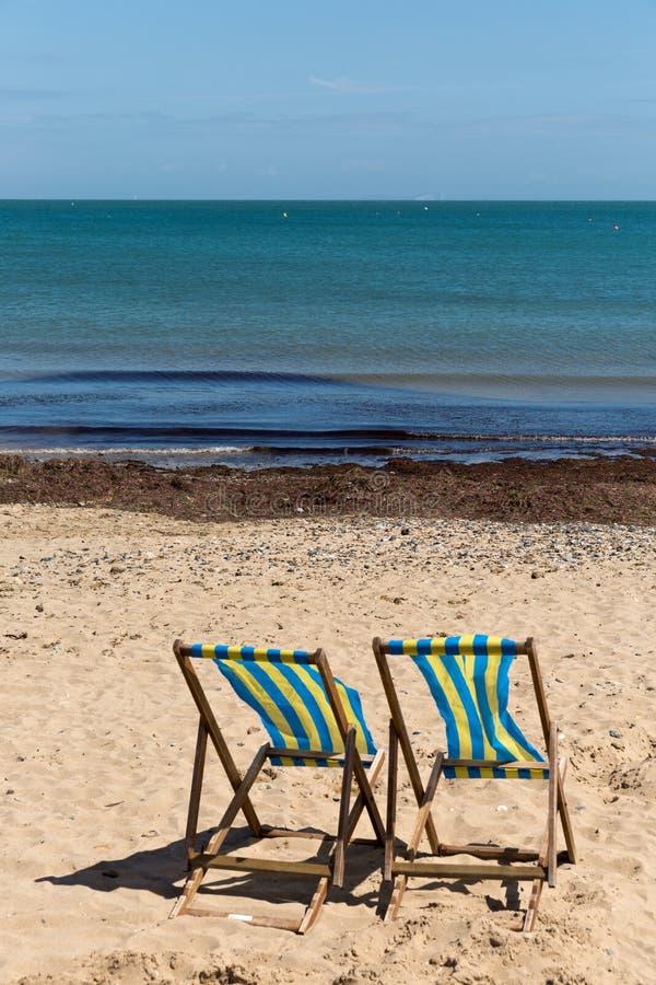 Twee blauwe en witte gestreepte ligstoelen op het zandstrand met zijn rug naar de camera royalty-vrije stock afbeeldingen