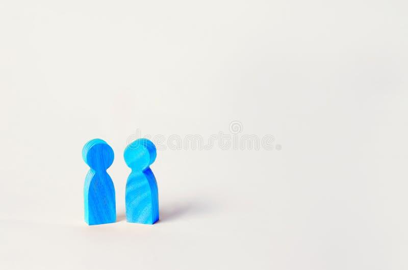 Twee blauwe houten cijfers van mensentribune op witte achtergrond twee personen van homoseksuele richtlijn het concept relaties b stock fotografie
