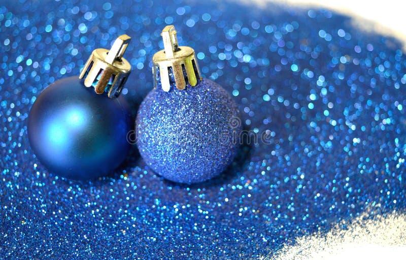 Twee blauwe Kerstmisballen op blauw schitteren op witte achtergrond royalty-vrije stock foto