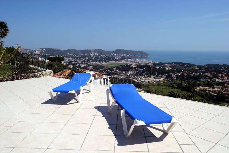 Twee blauwe sunbeds op terras in de zon met verbazende meningen van de oceaan stock afbeelding