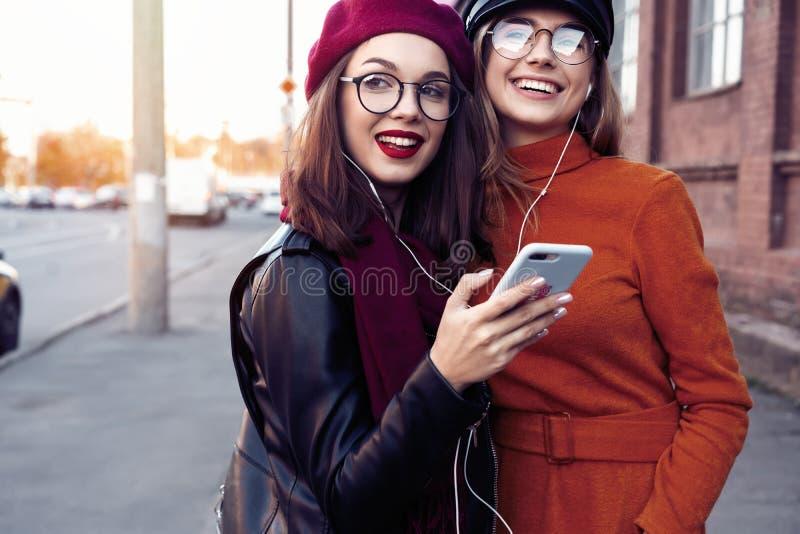 Twee blije jonge meisjes die terwijl het luisteren aan muziek op smartphone, stad openlucht dansen royalty-vrije stock foto's