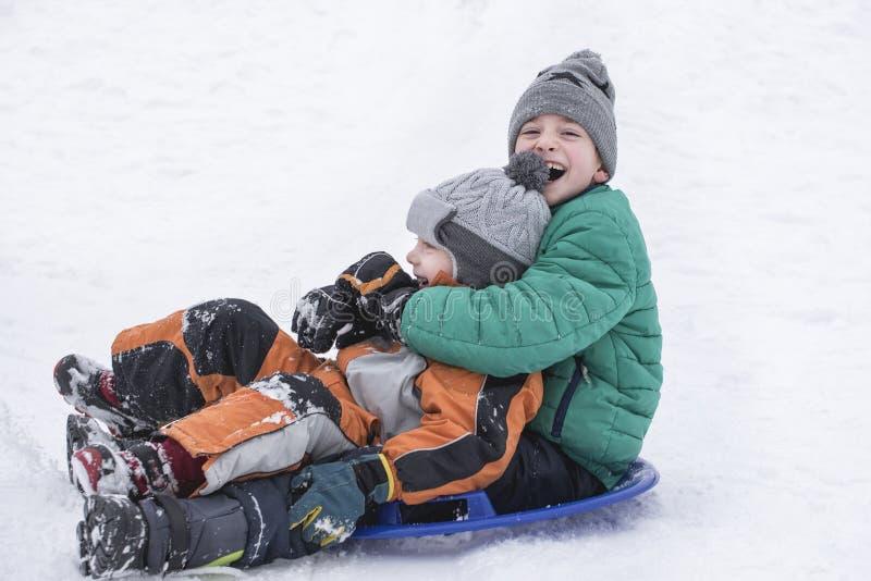 Twee blije jongens glijdt onderaan de heuvel op sneeuwschotel Broederlijke vriendschap De dag van de winter royalty-vrije stock afbeeldingen