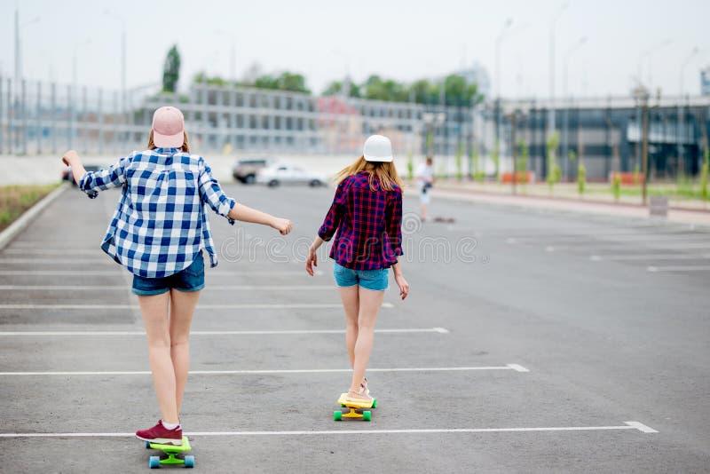 Twee blonde meisjes die geruite overhemden, kappen en denimborrels dragen longboarding op het lege parkeerterrein Sport en koel stock afbeeldingen