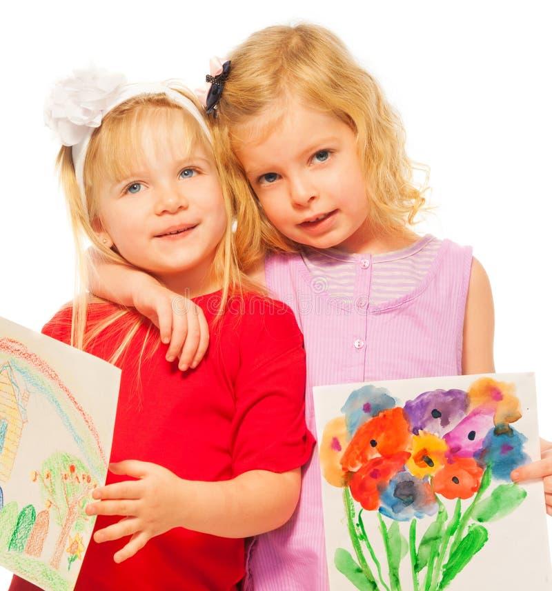 Twee blonde meisjes met hun schilderijen royalty-vrije stock foto