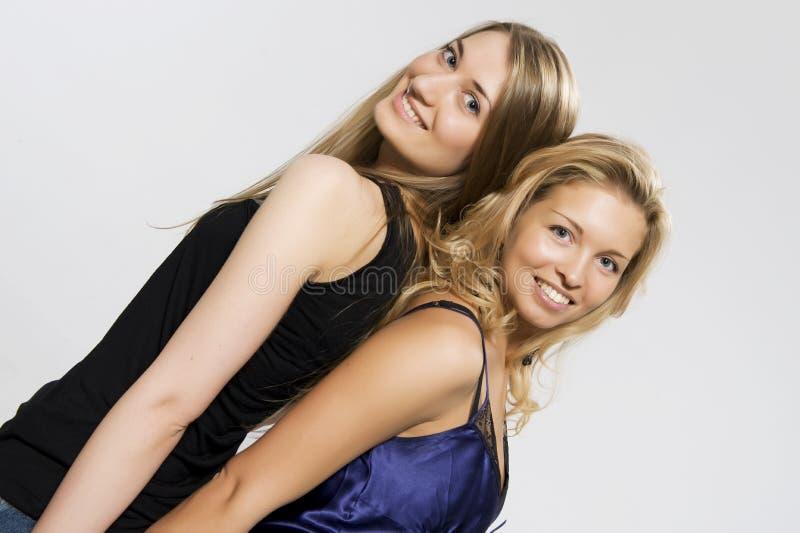 Twee blonden van rotatie aan de rug stock foto