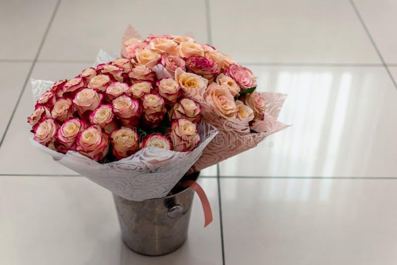 Twee boeketten van rozen in een emmer voor bloemen zijn op de tegelvloer stock afbeeldingen