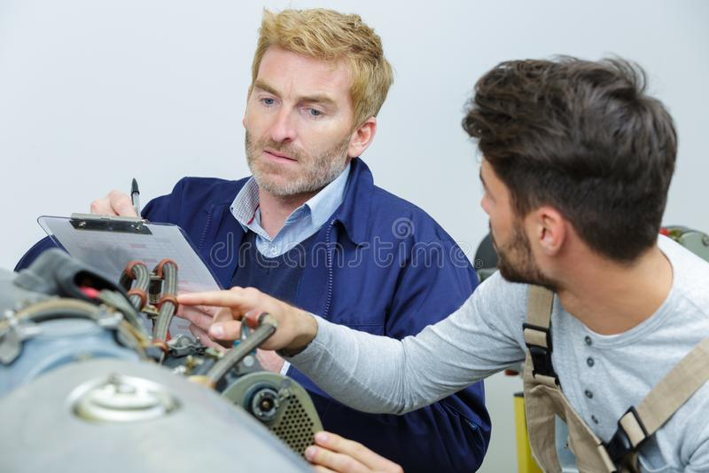 Twee boordwerktuigkundigen die aan vliegtuig werken royalty-vrije stock afbeelding