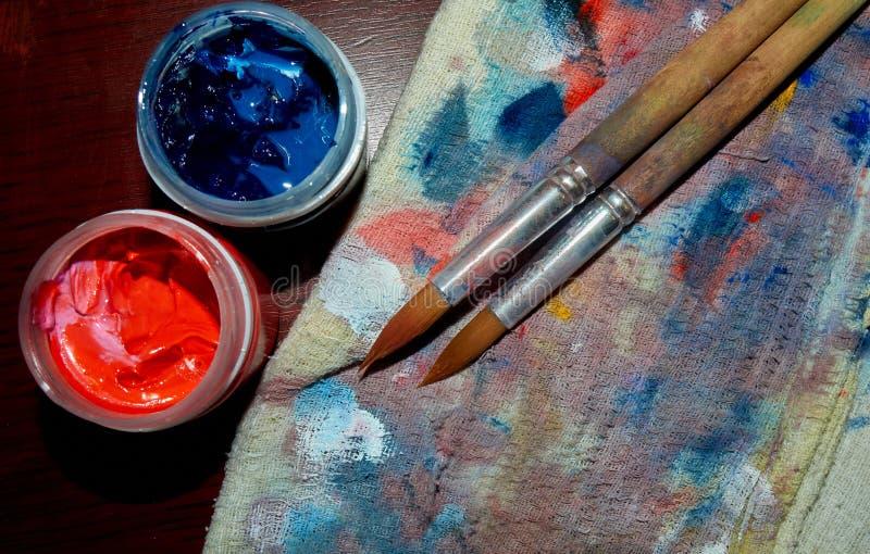 Twee borstels op het kleurrijke vod met twee gouacheblikken stock foto