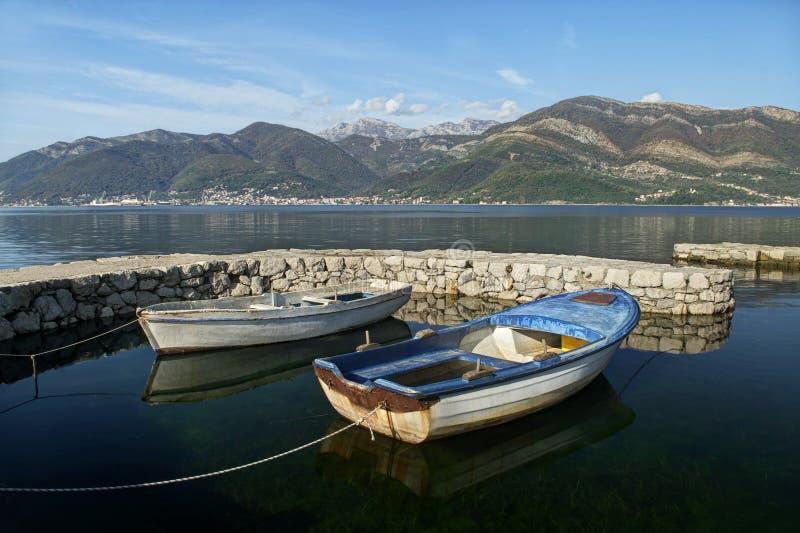 Twee boten in dok en bergen stock fotografie