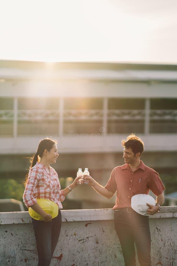 Twee bouwingenieurs vieren na het werk of project bij bouwwerf of fabrieks, man en vrouwen stotende waterflessen stock afbeelding