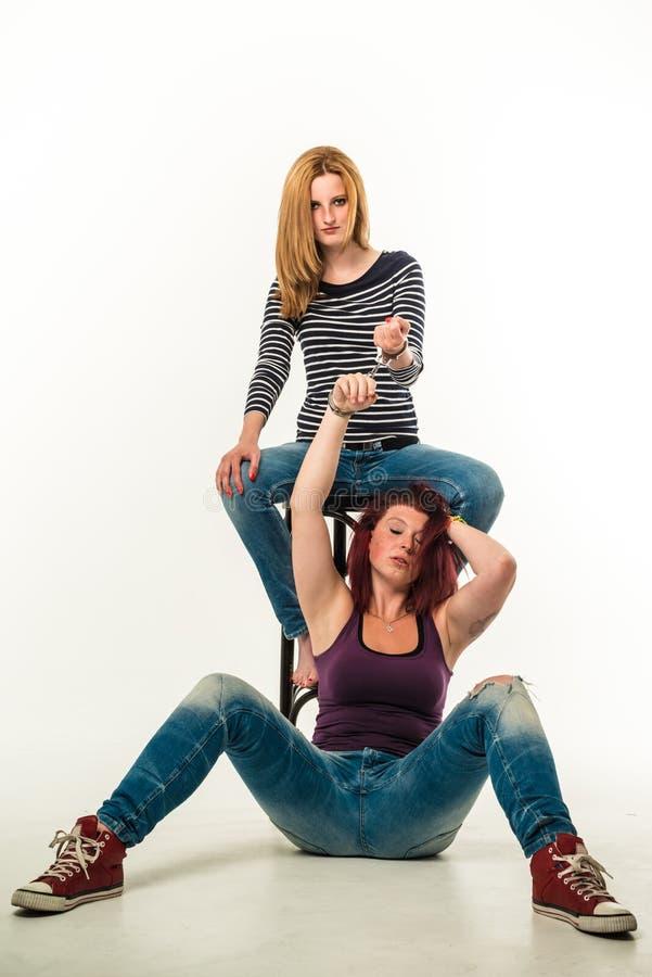 Twee boze die vrouwen door een paar handcuffs worden verbonden stock foto's