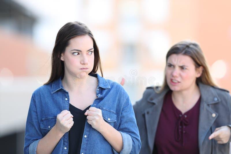 Twee boze vrienden die in de straat debatteren stock foto's