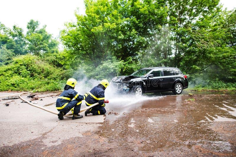 Twee brandbestrijders die een brandende auto na een ongeval doven royalty-vrije stock afbeeldingen