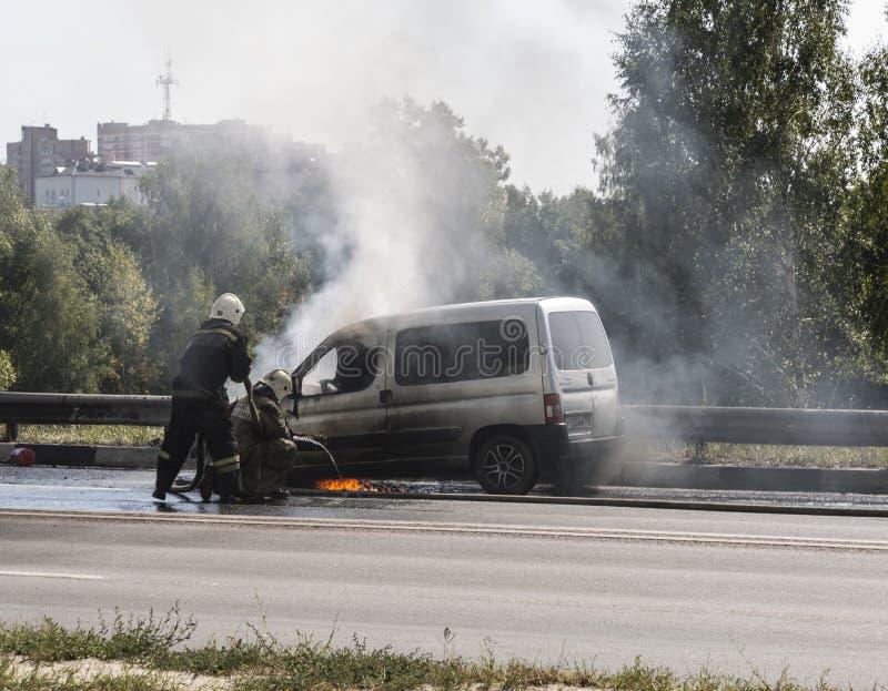 Twee brandbestrijders doven een brandende auto aan de kant van de weg Stad van Istra, het gebied van Moskou stock afbeeldingen