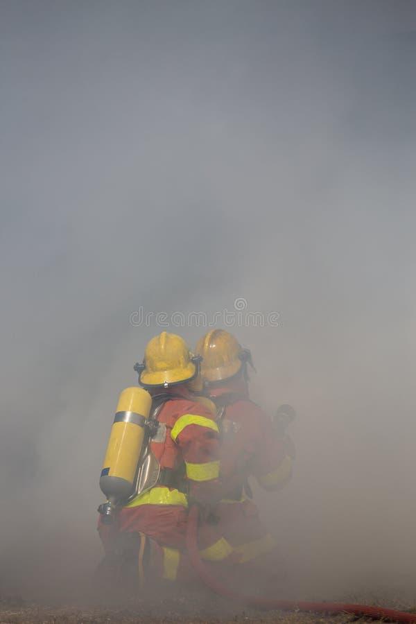 Twee brandbestrijders werkt rand met rook stock afbeeldingen