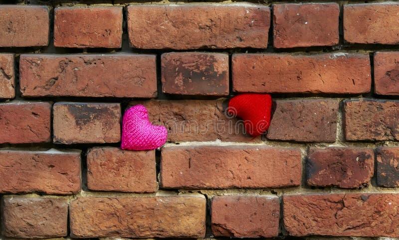 Twee breien rode harten en roze bevinden zich op een afbrokkelend oud rood stock fotografie