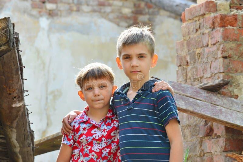 Twee broers bevinden zich dichtbij het geruïneerde huis, het concept natuurramp, brand, en verwoesting royalty-vrije stock foto