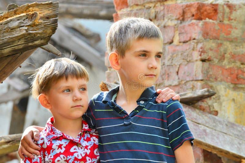 Twee broers bevinden zich dichtbij het geruïneerde huis, het concept natuurramp, brand, en verwoesting royalty-vrije stock fotografie