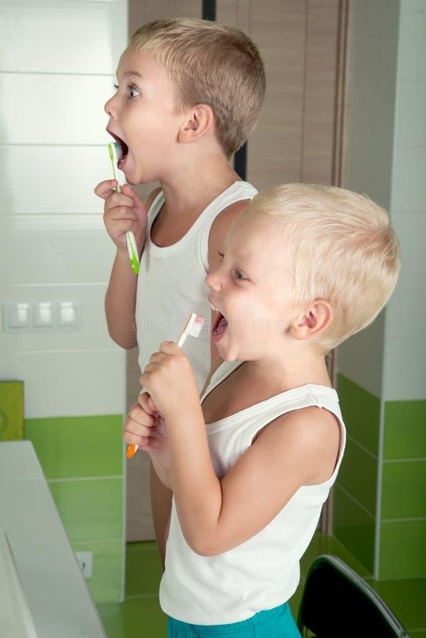 Twee broers borstelen tanden in de badkamers royalty-vrije stock afbeelding