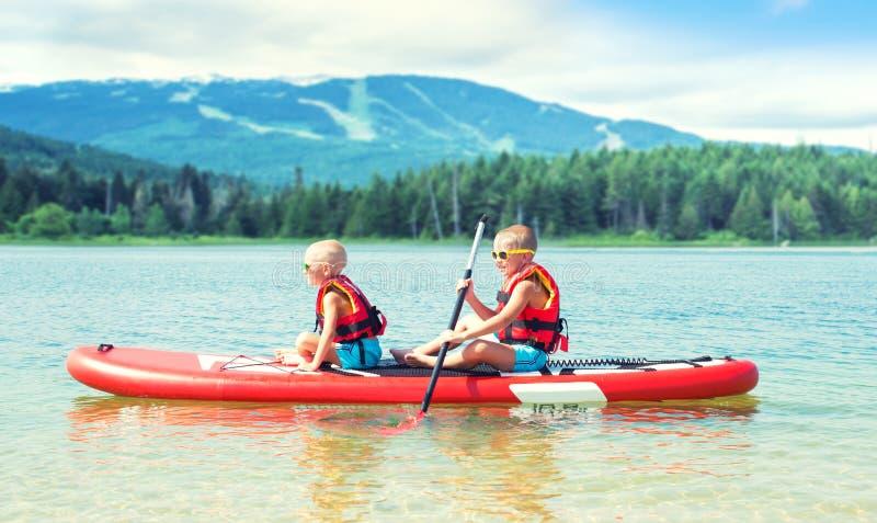 Twee broers die op tribune op peddelraad zwemmen Watersporten, actieve levensstijl royalty-vrije stock foto