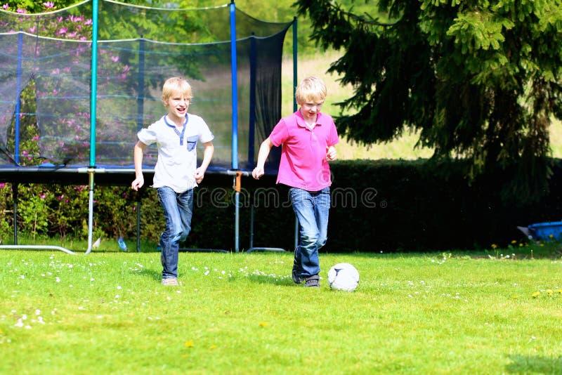 Twee broers die voetbal in de tuin spelen stock foto's