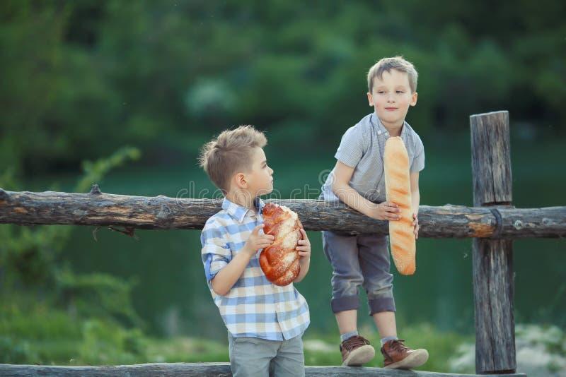 Twee broers eten zwart rond brood op een tarwegebied royalty-vrije stock foto's