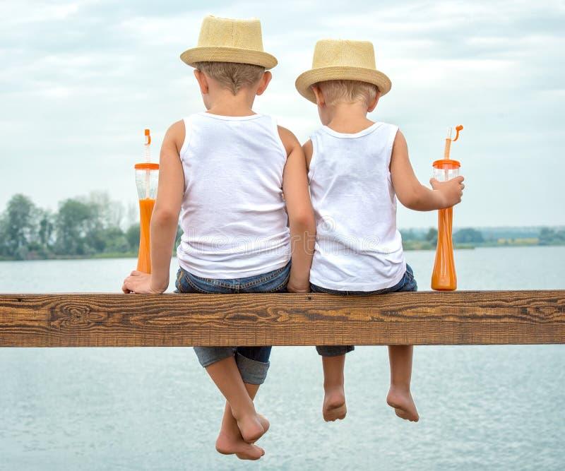 Twee broers slingerden hun benen van de houten pijler op het meer en drank verse sap royalty-vrije stock afbeeldingen