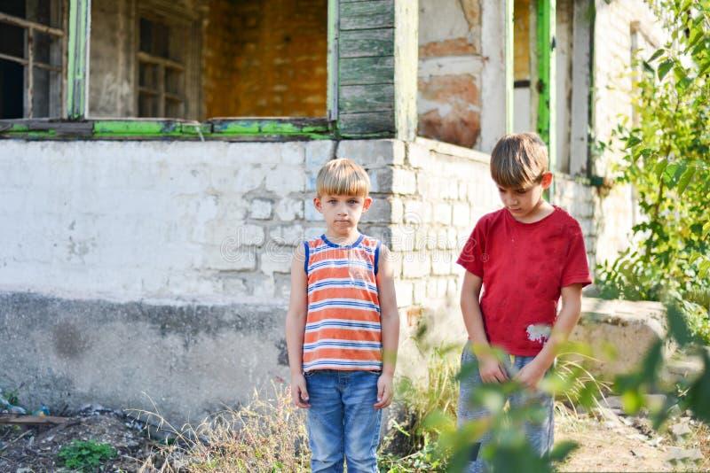 Twee broers staan in de buurt van een verbrand huis, die hun huizen zijn kwijtgeraakt als gevolg van vijandelijkheden en natuurra royalty-vrije stock afbeeldingen