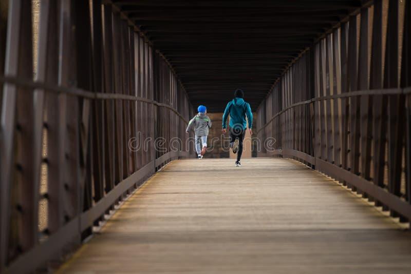 Twee Broers stellen een Race onderaan Brug in werking stock foto's