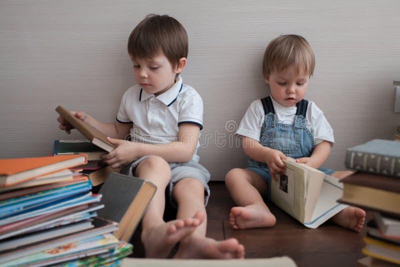 Twee broers zitten en bestuderen boeken stock fotografie