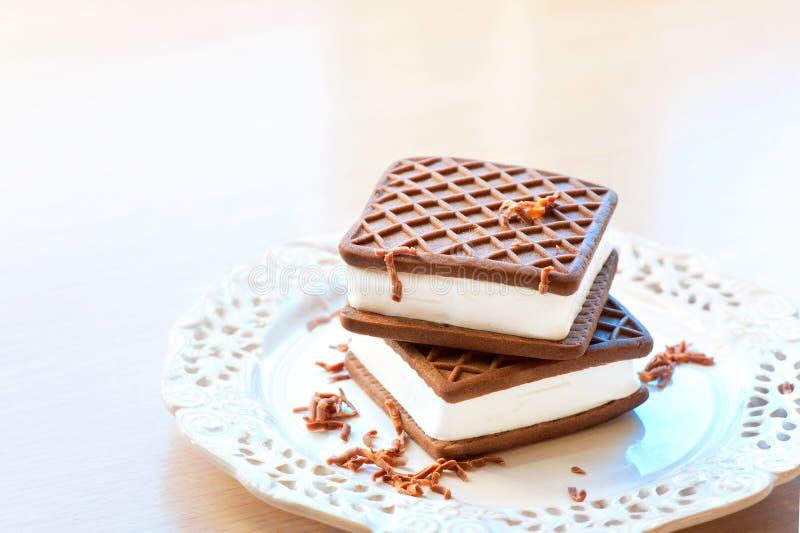 Twee bruine en witte roomijssandwiches Chocolade met vanille stock afbeelding