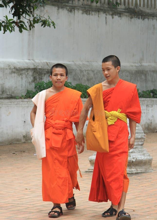 Twee buddistmonniken lopen binnen op de straat stock foto