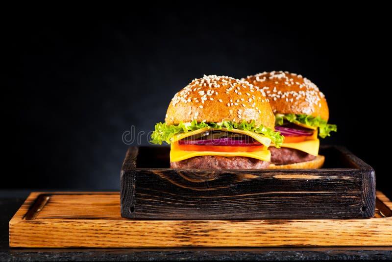 Twee burgerscheeseburgers met kotelet, kaas en groenten royalty-vrije stock afbeelding