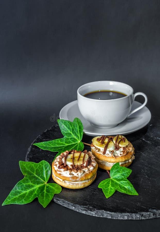 Twee cakekoekjes met room, banaan en chocolade en een kop van koffie op een leischotel op een zwarte die achtergrond, met groen w stock foto's