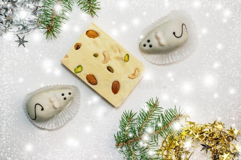 Twee cakes in de vorm van witte muizen en een marsepein-en-kaas Turkse verrukking die op de groene takken van een Kerstboom ligge royalty-vrije stock afbeeldingen