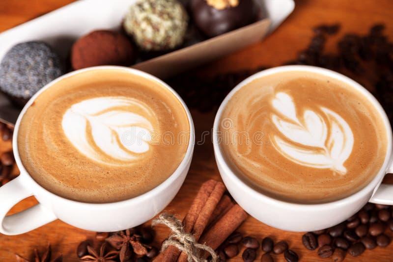 Twee cappuccinokoppen met latte-kunst op een houten lijst met verspreide koffiebonen en cakes Vreugde met een Kop van koffie stock fotografie
