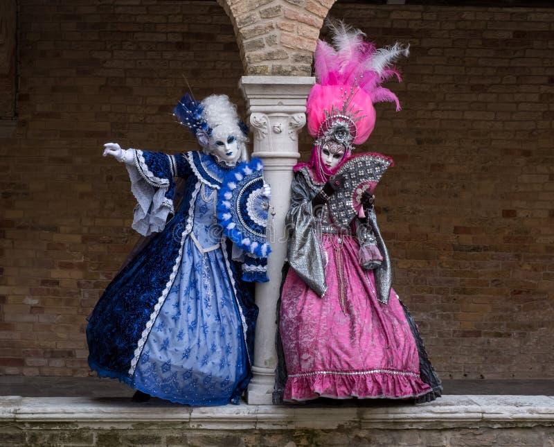 Twee Carnaval-goers die helder gekleurde maskers en kostuums dragen in Venetië Carnaval royalty-vrije stock foto