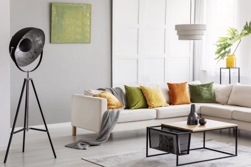 Twee ceramische vazen die zich op moderne koffietafel in heldere woonkamer met elegante hoekbank, industriële lamp en gouden kalk stock foto