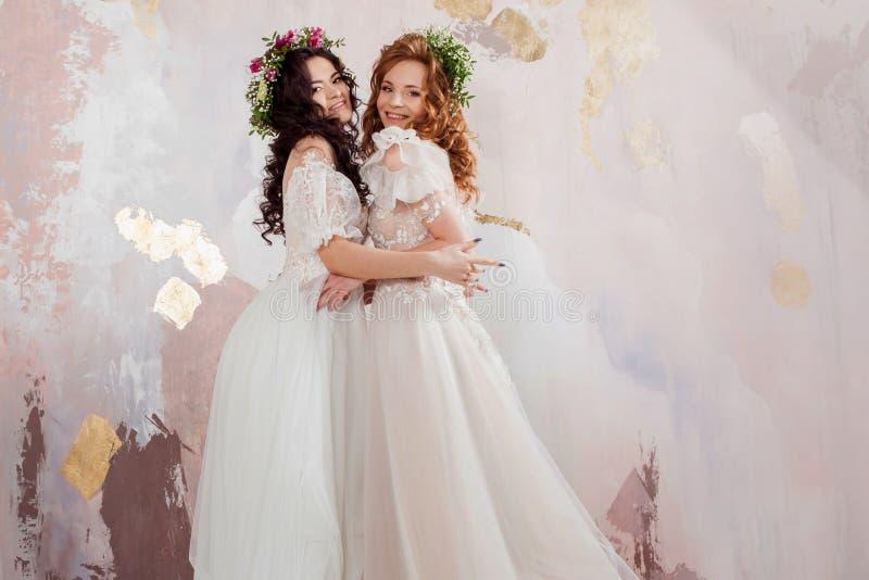 Twee charmante bruiden in mooie de lentekronen op hun hoofden Mooie jonge vrouwen in huwelijkskleding royalty-vrije stock fotografie