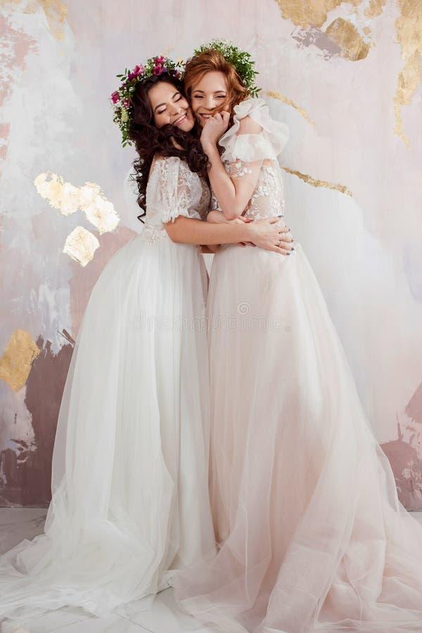 Twee charmante bruiden in mooie de lentekronen op hun hoofden Mooie jonge vrouwen in huwelijkskleding stock foto's