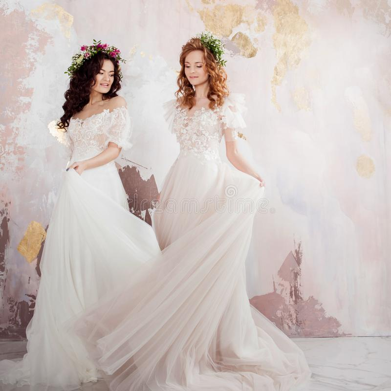 Twee charmante bruiden in mooie de lentekronen op hun hoofden Mooie jonge vrouwen in huwelijkskleding stock fotografie