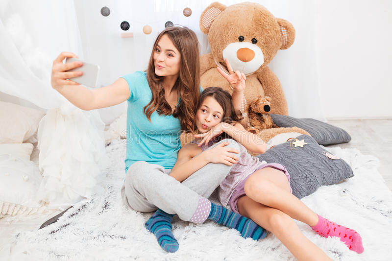 Twee charmante gelukkige zusters die eendgezichten maken en selfie nemen royalty-vrije stock afbeeldingen