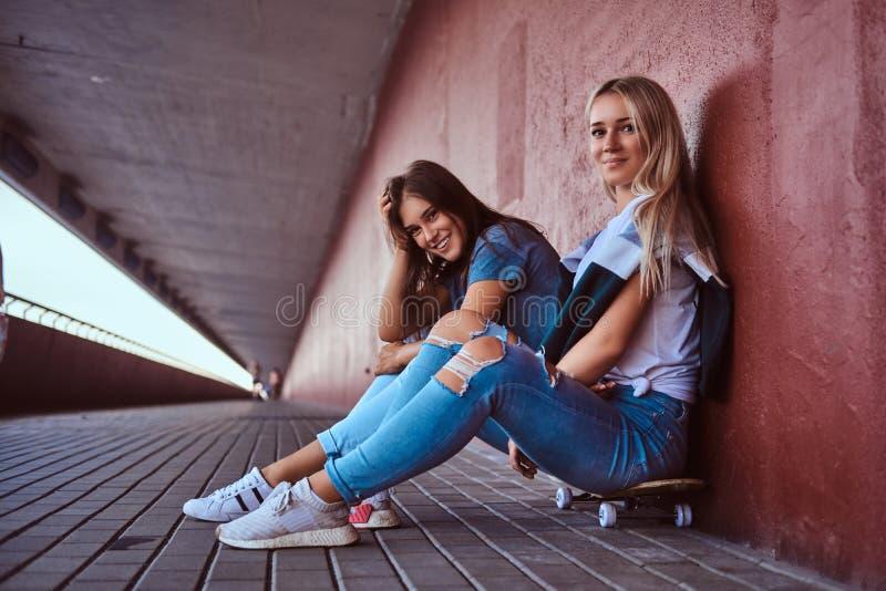 Twee charmante hipster meisjes die op skateboard zitten en op een muur bij de stoep leunen stock afbeelding