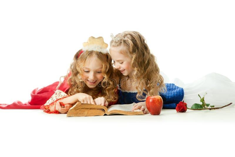 Twee charmante Kleine Prinsessen die het Magische Boek lezen stock fotografie