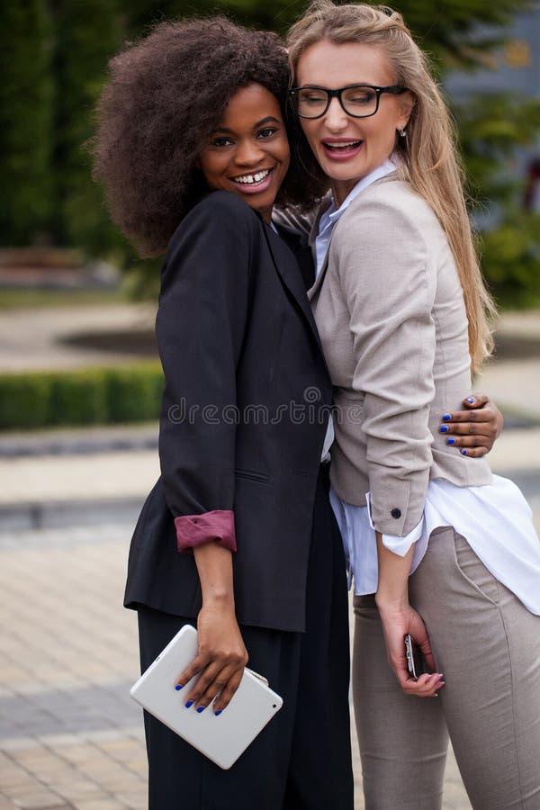 Twee charmante multirasonderneemsters koesteren gelukkig en glimlachen in park stock afbeeldingen