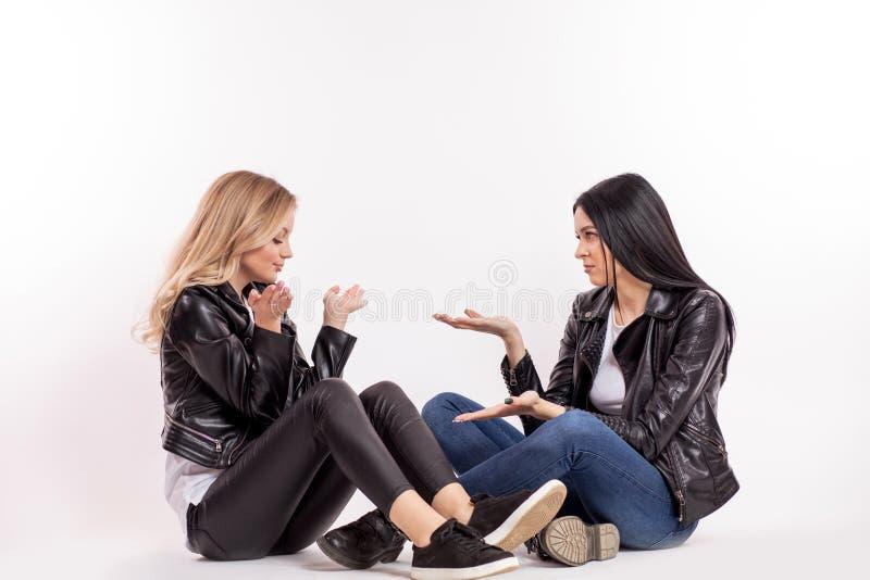 Twee charmante vrouwelijke vrienden die in zwart leerjasje iets bespreken royalty-vrije stock foto's