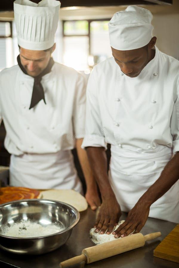 Twee chef-koks die pizza maken doug stock fotografie