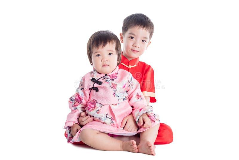 Twee Chinese kinderen die traditionele kostuumzitting op de vloer over wit dragen royalty-vrije stock afbeelding