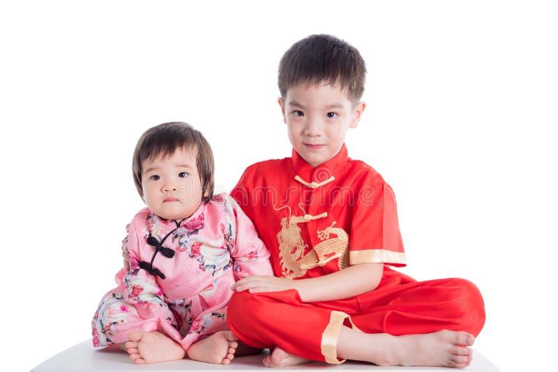 Twee Chinese kinderen die traditionele kostuumzitting op de vloer over wit dragen royalty-vrije stock foto